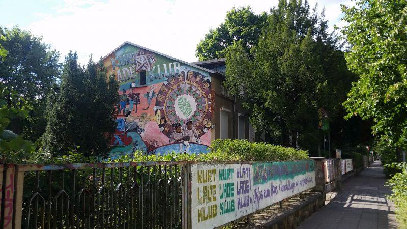"""Ein Gebäude, das bunt mit Graffiti bemalt ist. Um das Gebäude herum ein Zaun, an dem ein Banner befestigt ist, auf dem """"Kurt Lade Klub"""" steht. Um das Gebäude Bäume."""