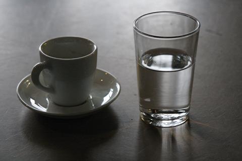 eine Espressotasse und ein Glas Wasser