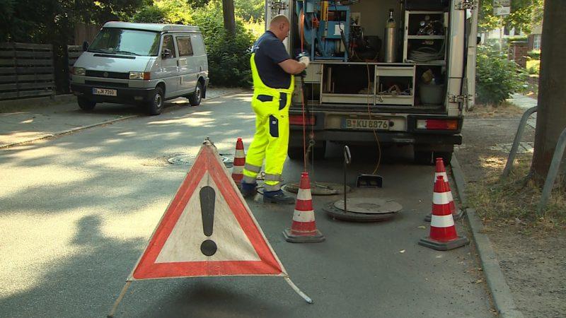 Ein Mitarbeiter der Berliner Wasserbetriebe arbeitet auf einer Straße an einem Gulli. Er steht vor einem Fahrzeug. Im Vordergrund ist ein Warnschild zu sehen.